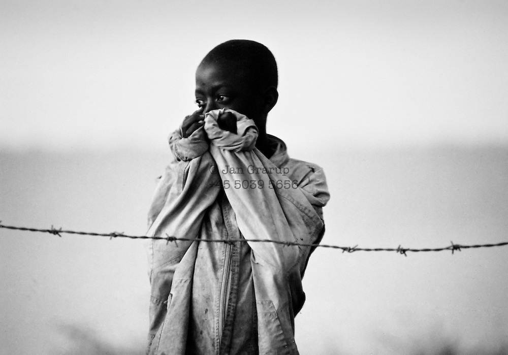 A tutsi refugee in a Red cross camp on the tanzanian/rwandan border.<br /> Apr.1994 -<br /> The sun had set over the rwandan capital Kigali as president Juvenal Habyarimana's plane approached the city's airport on 6.april 1994.Suddenly, out of the darkness, a rocket hit the plane and sent it crashing to the ground, killing everyone on board.over the next three month's, more than 800.000 rwandans would be murdered, many cut down with machetes, killed by neighbours and countrymen, in a ferocious ethnic genocide that was all but ignored by the international world.