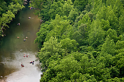 Paddlers enjoy a leisurely float down the Buffalo River in Arkansas. The view is from Big Bluff which is part of the Buffalo National River. Big Bluff is accessed from a side trail off the Center Point Trail.<br /> <br /> The 150-mile Buffalo River in northern Arkansas was the first river in the United States to receive the designation as a National River. The Buffalo National River, encompasses 135 miles of the river which is managed by the National Park Service. The river is a popular canoeing, kayaking, camping, and fishing destination. Popular destinations in the national river&rsquo;s boundaries include; Lost Valley, Hemmed-Iin-Hollow Falls (the highest waterfall between the Appalachian and Rocky Mountains, Indian Rockhouse, numerous caves and over 500-foot tall bluffs. The area is also home to Arkansas&rsquo; only elk herd.
