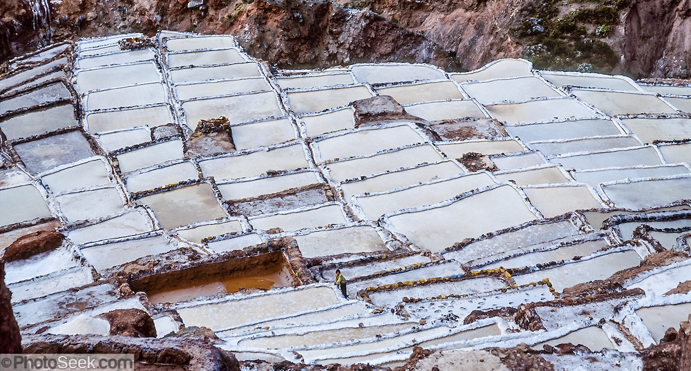 """Since pre-Inca times, salt farmers at the saltworks (salinas) near Maras have evaporated salty water from a subterranean stream in Peru, South America. A rough dirt road connects Maras (in the Urubamba/Vilcanota River Valley, Sacred Valley of the Incas) with Cuzco (40 km north) and other towns. The cooperative system of pond farmers was established during the time of the Incas, if not earlier, and is traditionally available to any person wishing to harvest salt. Intricate channels redirect water flow through several hundred ancient terraced ponds. As water evaporates from the sun-warmed ponds, it becomes supersaturated and salt precipitates as crystals. A pond keeper closes the water-feeder notch, allows the pond to go dry, then scrapes and carries away the dry salt. Salt color varies from white to a light reddish or brownish tan, depending on """"farmer"""" skills. Panorama was stitched from 2 overlapping photos."""