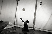 Dollo Ado, Ethiopia.October2011.<br /> A small mentally ill boy - plays with a balloon in his tent at the Hospital in &quot;Hilaweyn&quot; refugeecmp. Due to severe malnitrition many children arrive sick mentally as well as physically and are in need of special care from the medical staff.<br /> &rdquo; The drought in the horn of Africa is affecting more than 4.5 million people in Ethiopia. In addition, more than 140.000 refugees from Somalia have settled in camps in the border region between Somalia and Ethiopia. In the area around the border city Dollo Ado, four large refugee camps are already over crowded. A fifth camp is under construction due to the big influx still taking place. Many of the refugees are children, arriving severely malnutritioned. The mortality rate among small children has been brought down, but still children are dying on a daily basis...<br /> The four camps &ndash;Hilaweyn,Kobe, Malkadida and Bokomayo are now hosting more than 120.000 refugees and more are coming daily....