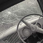 Angled, black and white shot of dashboard and broken windshield of abandoned Chevy pickup truck. Shot in rural San Diego county.
