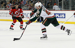 Mar 20, 2009; Newark, NJ, USA; Minnesota Wild defenseman Marc-Andre Bergeron (47) makes a pass while being defended by New Jersey Devils center John Madden (11) during the second period at the Prudential Center.