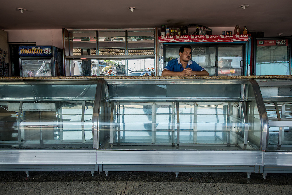BOCA DE UCHIRE, VENEZUELA - JUNE 16, 2016:  Bakery worker Dionny Ramírez, 36, poses for a portrait behind empty bread shelves. The bakery was looted by an angry crowd of hundreds of people on June 7th, while Mr. Ramírez was working.  He said the crowd was too big for workers to stop them, so he grabbed the panini press, one of the most valuable items in the bakery, and kept it safe. He said after the experience, it is difficult for him to trust his neighbors.  PHOTO: Meridith Kohut