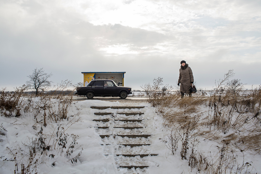HIRNE, UKRAINE - DECEMBER 8, 2014: A car passes a pedestrian on the road between Donetsk and Luhansk in Hirne, Ukraine. CREDIT: Brendan Hoffman for The New York Times