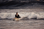 A boogie boarder looks pensive as he rides his board into the beach, Rockaway Beach, Queens, NY.
