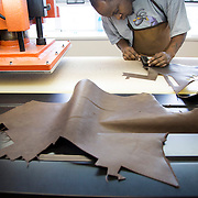 DETROIT, MI - OCTOBER, 30: Damond Love, 40, of Detroit, MI, fills in for a sick employee cutting leather for watchbands at the Shinola factory in Detroit, Michigan, Thursday, October 30, 2014. Love started out on the leather assembly line and now works as Quality Control for Leather. (Photo by Jeffrey Sauger)