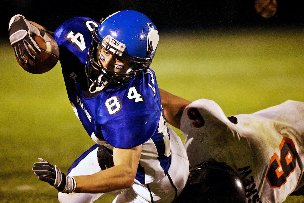 Coeur d'Alene High's Addison Johnson reaches for extra yardage as he is being tackled by Johnny Haskew from Post Falls during the second half of the Viking's 63-35 win Friday over the Trojans.