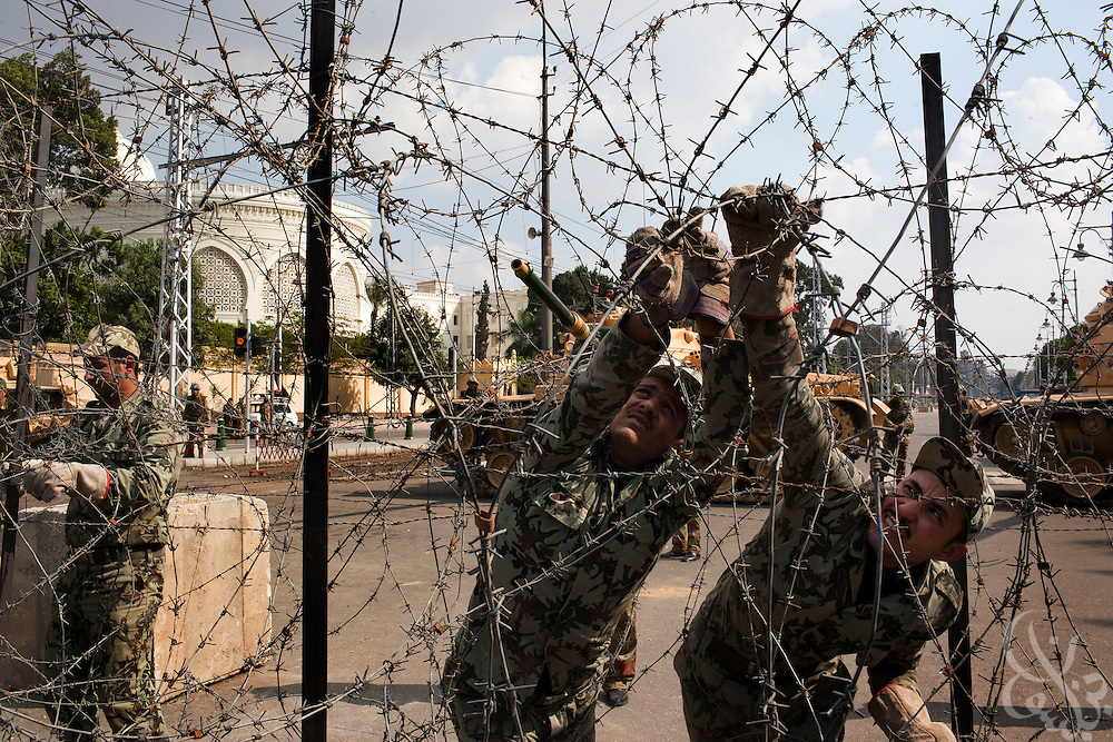 Egyptian military soldiers reinforce the barbed wire barricade outside the Orouba Presidential Palace February 11, 2011 in the Heliopolis district of Cairo, Egypt. Protesters marched Friday on a number of public buildings including the palace in an effort to spread their ongoing protests that are now in their 18th day.(Photo by Scott Nelson)