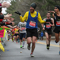 Pierre-Michel Arcand (2518), of Verdun, Quebec, reacts to the crowd outside Wellesley College as Juan Carlos Soto (904) of Deltona, Florida, blows kisses while running the Boston Marathon, Monday, April 20, 2015.