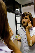"Wittaya Jannoi (21) fixing his make-up during a breack between classes. He is a marketing student .and hopes to change his gender after he finishes his studies at Suan Dusit university.  He sais: ""I'm .happy here. We can be ourselves because we don't have to hide. My mother said, 'Graduate first, .then you can do what you want'."" Like many transgender students, he learnt about the university .through the beauty pageant. ""I couldn't wait to come here."".In Suan Dusit University in Bangkok, ladyboys feel free to be themselves by getting dressed in .girls' uniforms and behaving in a feminning way. The University's policy of accepting them as .equal to other students, has made it so popular that it now has about 100 transgender students .studuing in it's faculties."