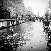 A man paddles down one of the canals in central Amsterdam, a sign of possible future transport for the locals of Amsterdam. Image © Angelos Giotopoulos/Falcon Photo Agency.