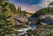 A nightscape photographer shooting at Elbow Falls on the Elbow River, in Kananaskis Country, Alberta, with the waxing gibbous Moon providing the illumination.