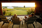 Couple enjoys a glass of wine overlooking vineyards at Rogue Valley Winery near Ashland, Southern Oregon