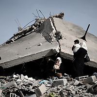 """A Palestinian family sits on the rubble of their destroyed house following Israel's 22-day offensive in Gaza on January 26, 2009 in the northern Gaza Strip district of Jabalia. A senior EU official touring Gaza blasted the """"abominable"""" destruction in the enclave and said its """"terrorist"""" Hamas rulers bear overwhelming responsibility for the war."""