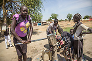 Students fetch water from a well at the Machakos Primary School in Bentiu, South Sudan. After two years of closure due to threats from unexploded ordnance, UNMAS surveyed and cleared the school compound in July 2015 allowing the school to reopen and the pupils to return to their studies.<br /> <br /> Photo: UNMAS/ Martine Perret