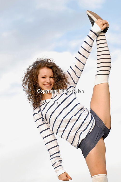 Cute young woman performing hard stretching exercise