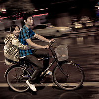 A young couple rides a bike through downtown Yangzhou, China, a suburb city of Shanghai and major producer of photovoltaic cells for solar power.