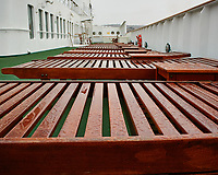 Rain covered outdoor teak deck chairs on the port side aft deck of the MV World Odyssey. Waiting for all of the students so the ship can depart from Ensenada, Mexico.  Image taken with a Nikon N1 V3 camera and 10-30 mm lens (ISO 200, 10 mm, f/3.5, 1/320 sec).