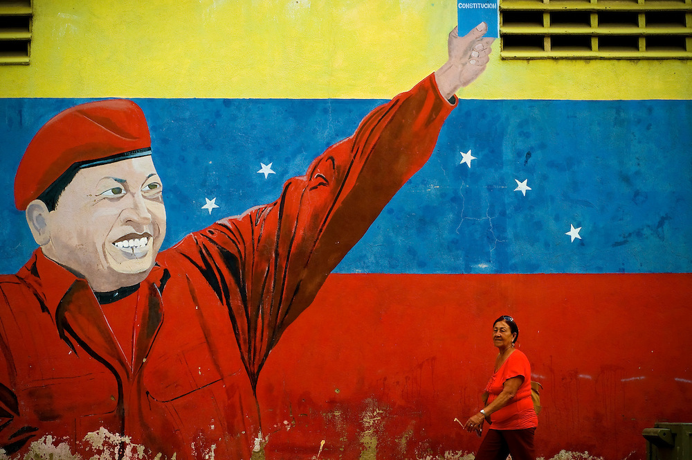 A woman passes a mural of Venezuelan President, Hugo Chavez, in Catia, a slum in Caracas, Venezuela. The Venezuelan government commissions collectives of graffiti artists to plaster the city in murals and stencils that promote the Bolivarian revolution and Chavez's socialist political agenda.