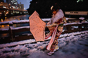 20 year old girl dressed in kimono, on her way to the station after a coming of age ceremony during a cold snow day in Tokyo.