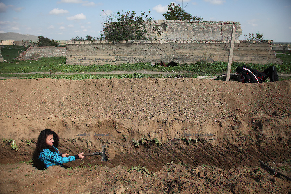 A female armenian volunteer supports the army and bury a new trench near the frontline of Nagorno Karabkh to Aserbaijan.