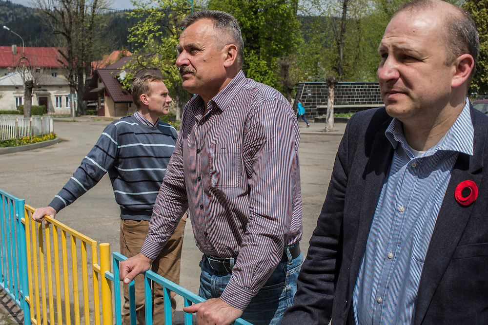 SKOLE, UKRAINE - MAY 1, 2015: Employees of the organization Dolya, Ostap Kozak, archivist, Volodymyr Kharchuk, deputy director, Svyatoslav Sheremeta, director, from left, stop to look at a memorial plaque to a local man killed in the 2014 anti-government protests in Kiev in Skole, Ukraine. Dolya was formed to excavate and repatriate remains from World War II, though its focus is often on locating the graves of Ukrainian partisans killed by Soviet forces. CREDIT: Brendan Hoffman for The New York Times
