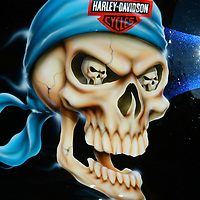 A skull graphic is painted on the gas tank of a Harley-Davidson motorcycle in downtown Milwaukee August 30, 2003. The legendary American motorcycle company is celebrating its 100th anniversary over four days.    REUTERS/Rick Wilking