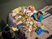 07 MARCH 2017 - KATHMANDU, NEPAL: A Newari Hindu priest (left) counsels a couple on the one year anniversary of the death of a family member at the ghats on the banks of the Bagmati River at Pashupatinath, a complex of important Hindu temples in Kathmandu. The Bagmati River runs through the complex. It is Nepal's most holy river, and this stretch of the river is like Varanasi in India. The river bank is lined with cremation ghats. Many Hindus, from both Nepal and India, make pilgrimages to Pashupatinath. It is traditional in Nepali Hinduism to mark the one year anniversary of a loved ones death to meet with a Hindu priest.     PHOTO BY JACK KURTZ