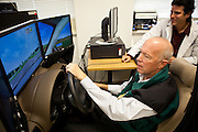 Steve Woodward, staff psychologist at the National Center for PTSD, left, tries out a driving simulator as VA Driving Rehabilitation Specialist Marc Samuels, right, looks on in Palo Alto, Calif., December 15, 2011.