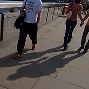 Boyfriend and girlfriend walk south over London Bridge having passed a man wearing a t-shirt with the slogan Make Your Move.
