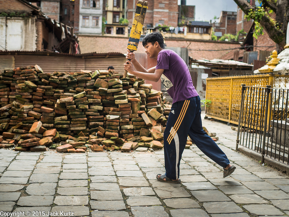 01 AUGUST 2015 - KATHMANDU, NEPAL: Boys practice cricket batting in front of a pile of bricks recovered for earthquake reconstruction. The Nepal Earthquake on April 25, 2015, (also known as the Gorkha earthquake) killed more than 9,000 people and injured more than 23,000. It had a magnitude of 7.8. The epicenter was east of the district of Lamjung, and its hypocenter was at a depth of approximately 15km (9.3mi). It was the worst natural disaster to strike Nepal since the 1934 Nepal–Bihar earthquake. The earthquake triggered an avalanche on Mount Everest, killing at least 19. The earthquake also set off an avalanche in the Langtang valley, where 250 people were reported missing. Hundreds of thousands of people were made homeless with entire villages flattened across many districts of the country. Centuries-old buildings were destroyed at UNESCO World Heritage sites in the Kathmandu Valley, including some at the Kathmandu Durbar Square, the Patan Durbar Squar, the Bhaktapur Durbar Square, the Changu Narayan Temple and the Swayambhunath Stupa. Geophysicists and other experts had warned for decades that Nepal was vulnerable to a deadly earthquake, particularly because of its geology, urbanization, and architecture.          PHOTO BY JACK KURTZ