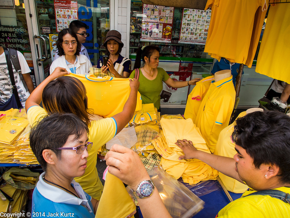 28 NOVEMBER 2014 - BANGKOK, THAILAND: People look at yellow shirts that are sold on the streets of Bangkok before the King's Birthday. Bhumibol Adulyadej, the King of Thailand, was born on December 5, 1927, in Cambridge, Massachusetts. The family was in the United States because his father, Prince Mahidol, was studying Public Health at Harvard University. He has reigned since 1946 and is the world's currently reigning longest serving monarch and the longest serving monarch in Thai history. Bhumibol, who is in poor health, is revered by the Thai people. His birthday is a national holiday and is also celebrated as Father's Day. He is currently hospitalized in Siriraj Hospital, recovering from a series of health setbacks. Thousands of people come to the hospital every day to sign get well cards for the King. People wear yellow at events associated with the King because he was born on a Monday, and yellow is Monday's color in Thai culture. It's also the color of the monarchy.       PHOTO BY JACK KURTZ