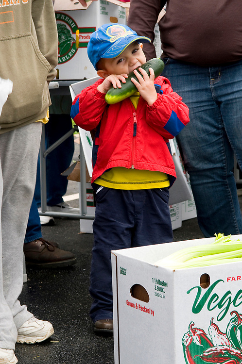 Jeremiah Amore, 2, can't wait to sink his teeth into a fresh cucumber Tuesday, September 29, 2009 in Crestline. Fresh produce was being distributed by the Second Harvest Food Bank.
