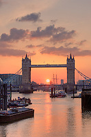 portrait image of tower bridge and setting sun behind
