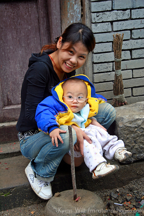 Asia, China, Guangxi, Daxu. A young mother's smile warmly encourages her baby to greet visitors to her ancient town of Daxu.