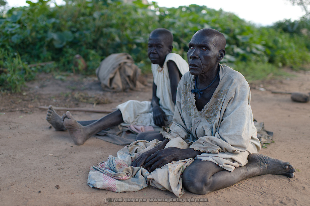 Elderly grandparents, Rosalie Ihaya (left) and Monica Itwari (who is blind) at the home of Helen Katerina Francis in Gunyoro village in Eastern Equatoria, South Sudan on 9 August 2014. Unable to fend for themselves, they rely on Helen, whose husband is a government soldier; she says that he has been away for a long time and provides no support to the family (locals indicate that soldiers frequently go unpaid), leaving her to fend for herself and their children and the elderly grandparents. Helen had been living with a brother who was helping to support them, but he recently passed away and the family is facing hard times—she described having fed them nothing but pumpkin leaves for the past week.