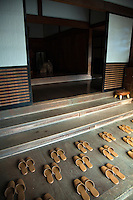 """Japanese Slippers carefully placed for guests arrival at """"engawa"""" or entrance.  Visitors to Japanese homes and temples are required to remove their shoes at the entrance, replacing them with hallway slippers such as these before entering.  Many young Japanese are happy to ignore the slippers and just walk around in ther sock or barefoot except in colder months."""