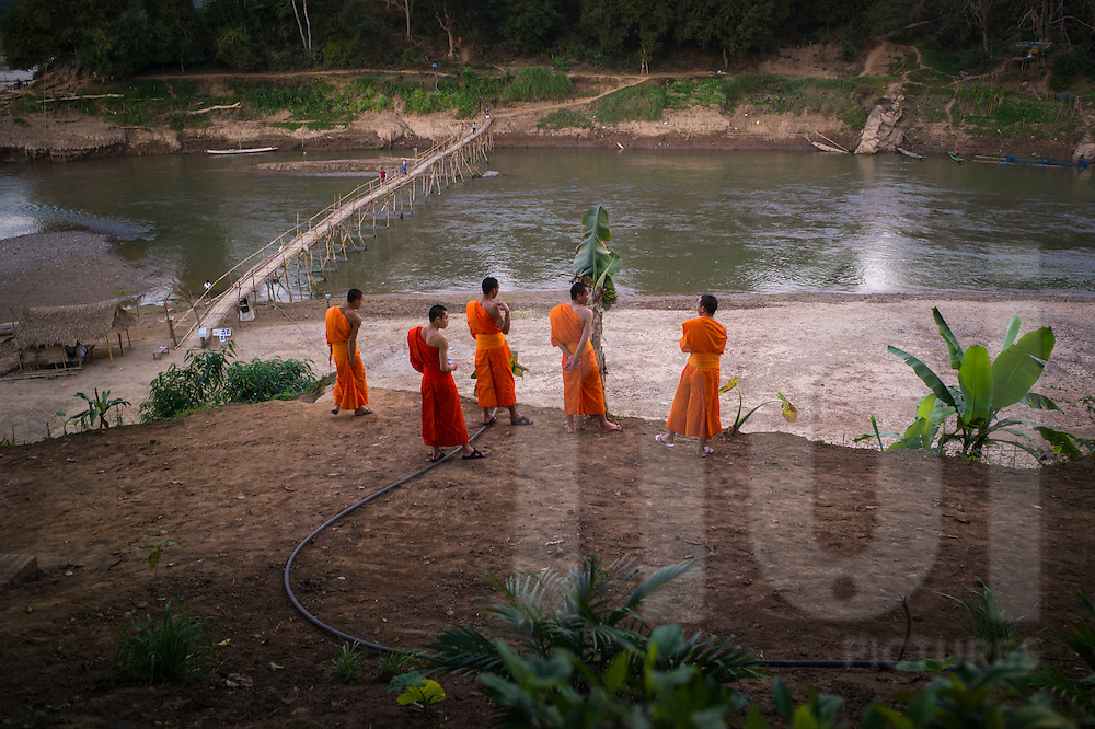Monks gather along the river bank of the Mekong at sunset, Luang Prabang, Laos, Southeast Asia
