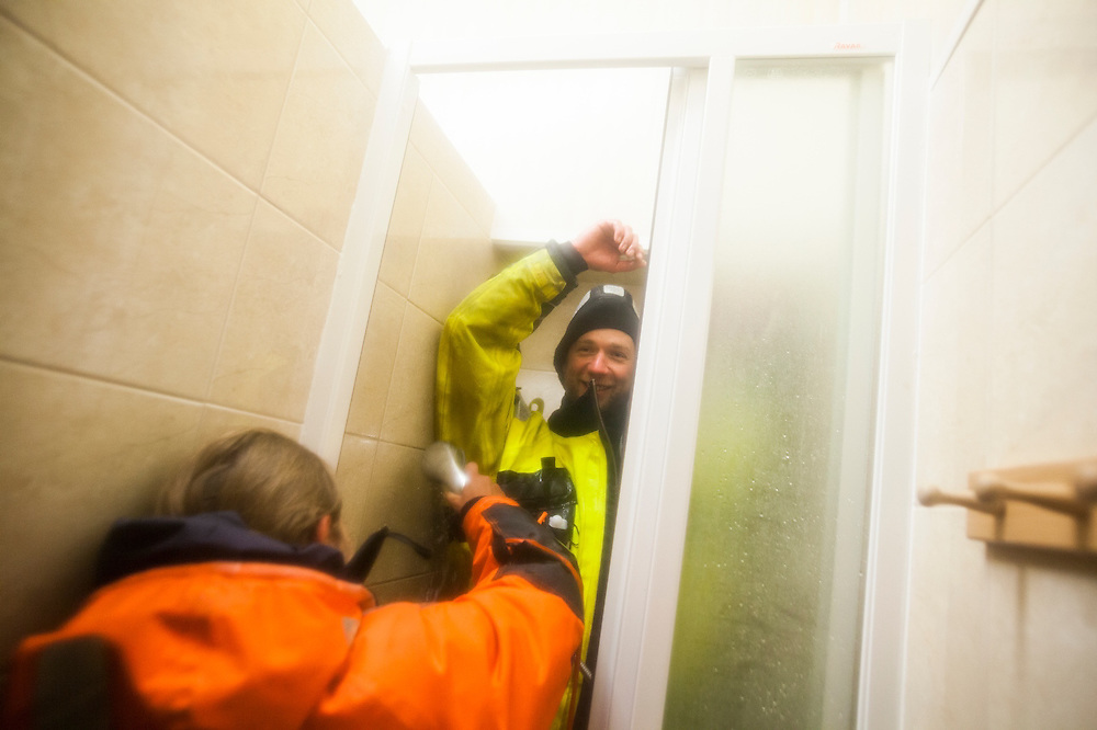 Agnieszka Piechota rinses salt off Dariusz Ignatiuk's survival suit in the shower of the Polish Polar Station, Hornsund, Svalbard before it is placed in storage until the next field season.