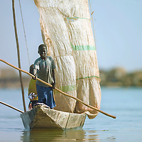 A boy steers a small sailboat on the Niger river, Mali. Western Africa's most important river springs in Guinea, stretches over four thousand kilometers and crosses Mali, Niger, Benin and Nigeria. Its basin covers over 7% of Africa's landmass. The river's inner delta, in central Mali, is a swampy region which floods annually making it very productive for fishing and agriculture.
