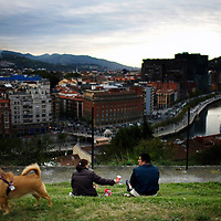 An immigrant couple arguing in a park overlooking Bilbao.