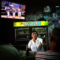 "A woman serves a beer at a salsa bar in the old city of Cartagena, Colombia. This photo is part of a project entitled, ""Macondo: Journeys in García Márquez's Colombia"" which documents the people and places on Colombia's Caribbean coastal region that helped to influence the work of Colombian author Gabriel García Márquez, the Nobel-prize winning author of One Hundred Years of Solitude. (Photo/Scott Dalton)"