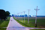 Two kids ride their bikes down a country road shortly after sunset on a warm summer evening in rural Illinois.