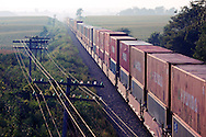 A solid train of import ocean containers moves east toward Chicago, passing across the hazy summer plains west of Miledgeville, IL.