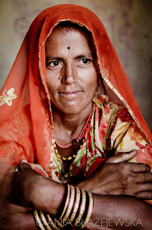 India, Thar desert. A woman wearing an orange dress. She lives in a small village in Thar desert near Jaisalmer.