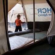 Adnan, 20 months, walks outside of their tent. Zaatari Camp for Syrian Refugees, Jordan, November 2013.