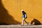 Man walking in front of yellow wall; San Miguel de Allende, Guanajuato, Mexico.