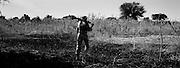 A goverment soldier walking thru a burnt village. in eastern Darfur.