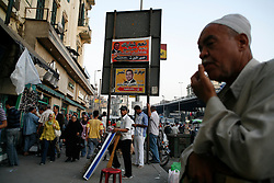 Street vendors in Cairo stand in front of posters of Egyptian President Hosni Mubarak.