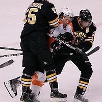 Boston, MA - Boston Bruins defenseman Johnny Boychuk (55) and center Patrice Bergeron sandwich Philadelphia Flyers defenseman Kimmo Timonen in the first period at TD Garden on December 11, 2010.   Photo by Matthew Healey